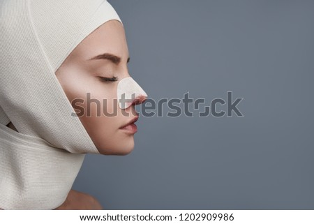 Head with bandages. Calm young lady sitting with her eyes closed and having bandages on the head and blood on the nose