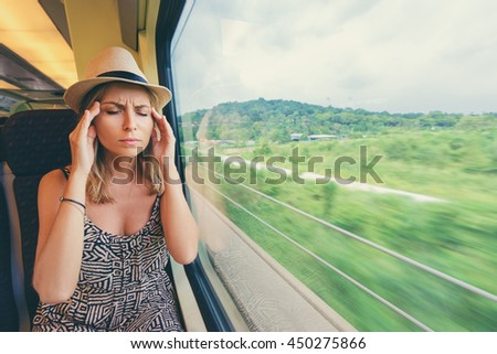 Headache and motion sickness. Stressed and tired young woman sitting near the window while travelling by train.