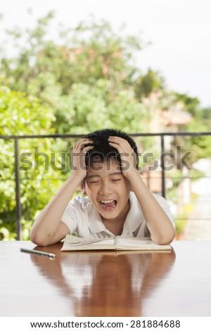 headache boy, an Asian young boy squeeze his head for homework like crazy