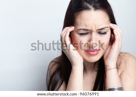 Headache concept - young woman suffering a migraine - stock photo