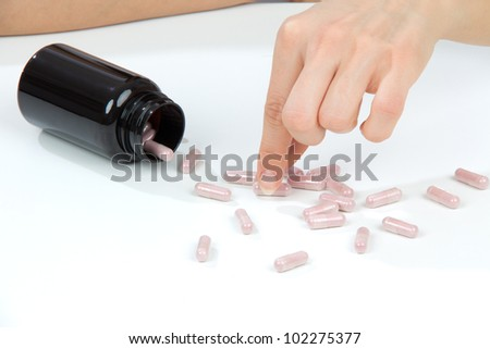 Headache hand with pills medicine tablets and glass of water against white background