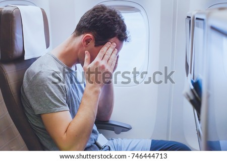 headache in the airplane, man passenger afraid and feeling bad during the flight in plane