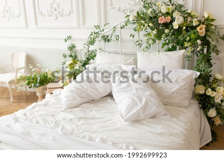 headboard decorated with flowers. white linens, white pillows