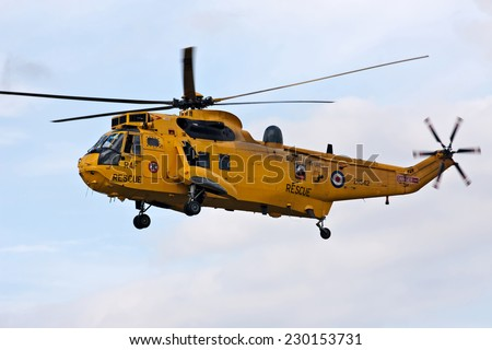 HEADCORN, UK - AUGUST 16: A Sea King helicopter from the Search and Rescue team of the RAF gives a low level display to the public at the Combined Ops show on August 16, 2014 in Headcorn