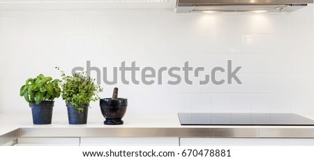 header of a fancy kitchen counter top with fresh herbs by the modern oven #670478881