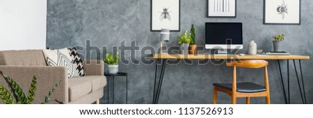 Header of a monochromatic living room interior with a cozy sofa and a stylish home office area with a wooden desk and posters on a gray wall #1137526913