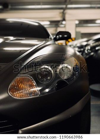 Stock Photo Headlamp headlight of grey car in the garage underground parking