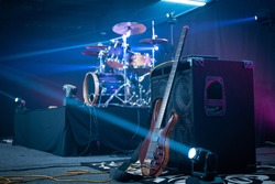 Headless bass guitar leaning on an amplifier. Drum kit in the background on a stage.