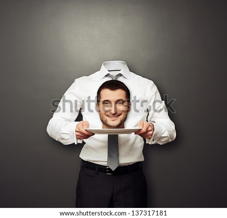 headless man holding smiley head on white plate over dark background