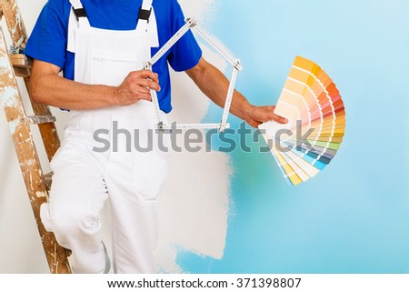 headless portrait of painter man with wooden vintage ladder showing a color palette and a yardstick shaped as an house