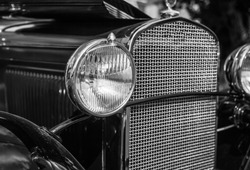 Headlight and grill of vintage automobile in black and white.
