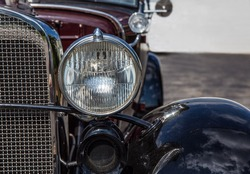 Headlight and grill of vintage automobile in color.