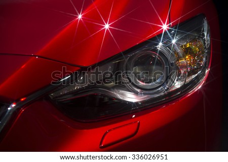 Headlight and hood of powerful sports red car with stars on bodywork, isolated on black  #336026951