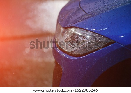 Headlight detail of blue car with water drop after car wash. Close up of headlamp. Side view shot from side of vehicle. Lens and reflector design. Detailing concept.