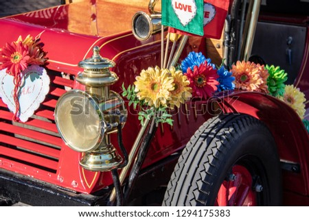 Headlight of an Old Classic Car Adorned with Flowers #1294175383
