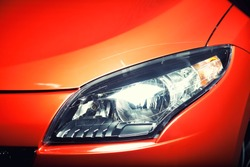 Headlight of an orange or red sports car, close up detail of the hood, fender, bumper and light, copy space