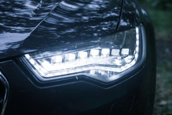 headlight of modern black car close up