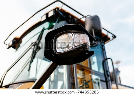 Headlight on the front of a powerful tractor excavator industrial machine at construction site - side view