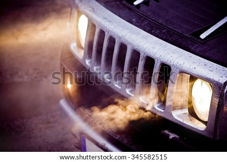 Headlights and chrome grille of a big powerful American SUV Hummer H2. Fog in the headlights of a black expensive off road car. Bad fuel milage or economy