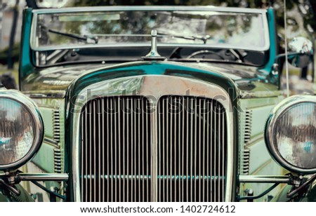 headlights and radiator of green old retro car closeup #1402724612