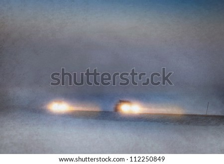 Headlights of cars driving in heavy snow storm