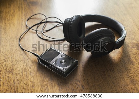 Headphone with music player on wooden table