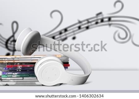 Headphones and compact discs on desk #1406302634