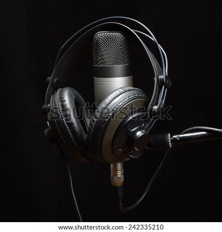 Headphones and condenser microphone isolated on the dark background