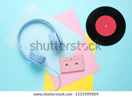 Headphones and earphones with audio cassettes on colored paper backgrounds. Retro style, minimalism. Flat lay. Top view.