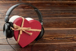 Headphones and heart-shaped gift box. Earphones and red gift box with copy space. Music gift concept.