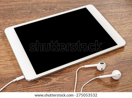 Headphones and tablet computer are on the table
