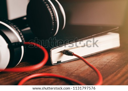 Headphones are placed on the book.Listening skill.Converting the contents of a book into an audio file.Listening to podcasts.