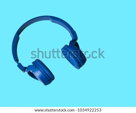 Headphones. Earphones on blue background. Headphones for music sound. Isolated on blue background. Blue headphones on blue background.