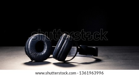 Headphones in the spotlight. The concept of music and bloggers. May illustrate a streaming report. #1361963996