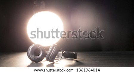 Headphones in the spotlight. The concept of music and bloggers. May illustrate a streaming report. #1361964014