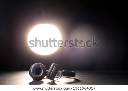 Headphones in the spotlight. The concept of music and bloggers. May illustrate a streaming report. #1361964017