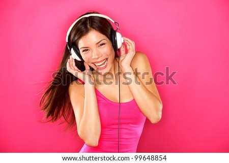 Headphones music woman dancing listening to music on mp3 player or smart phone. Fresh energetic happy multiracial Asian Chinese / Caucasian brunette dancer on pink background.