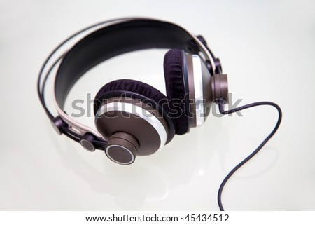 Headphones on a whiteand reflective background - stock photo