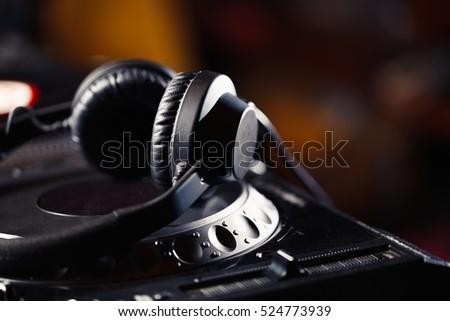 Headphones on CD music disc player for DJ. Top class audio equipment for night club concert.Professional disc jockey hardware