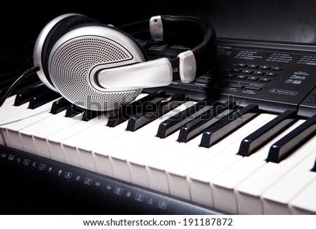 Headphones on musical synthesizer keyboard. Headphones on electronic piano