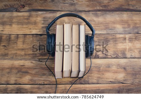 Headphones on the Pile of Books on the Wooden Table. Audiobooks. Learning through Audiobook. Stockfoto ©