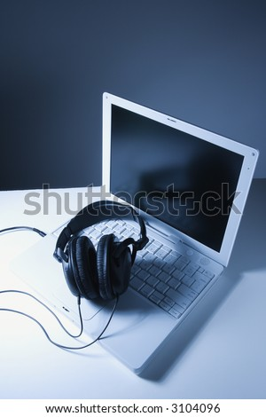 Headphones placed on laptop computer.