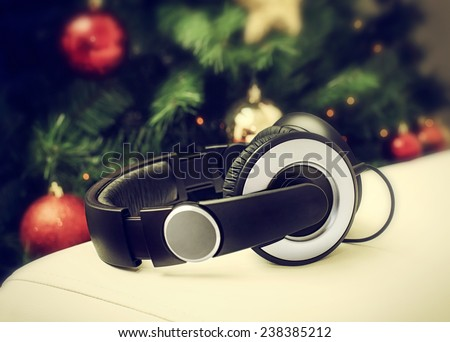 Headphones resting on a white leather sofa near the Christmas tree. Concept of Christmas music.