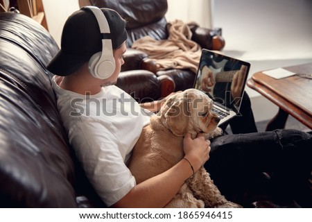 Headphones. Young man, student and his cute dog, pet American Cocker Spaniel sitting at home and listening music using laptop, smartphone. Office workplace, remote work, e-learning, indoors concept.