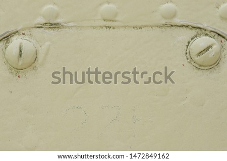Photo of Heads of rivets and screws under a layer of old paint, macro shot. Abstract background image of muted khaki color.  The surface of an old military equipment. Erased serial number in the main part.