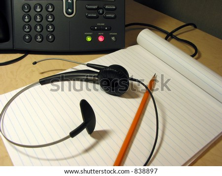 Headset, pencil and notepad on the office desk with IP phone in the background