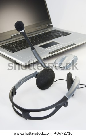 Headset with laptop and computer mouse on white desk