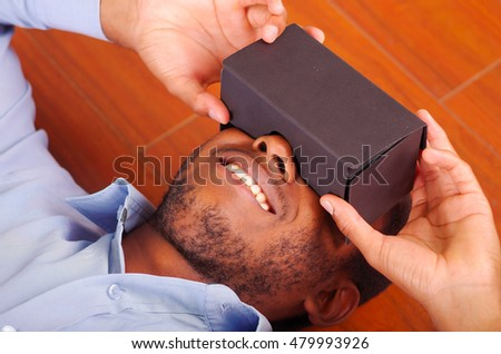 Headshot man lying down on wooden floor playing with virtual reality mobile device covering eyes #479993926