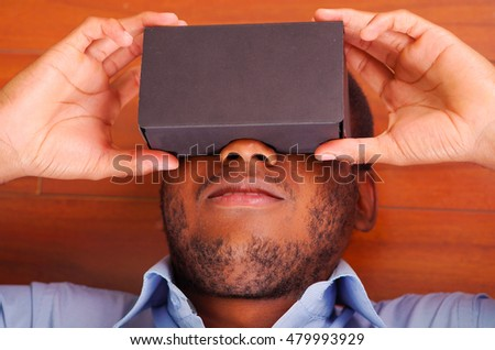Headshot man lying down on wooden floor playing with virtual reality mobile device covering eyes #479993929