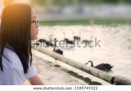 Headshot of a Thai little girl with long black hair and eyeglasses sitting at the lakeside looking away. Blurred scene of black swans swimming in the lake in the background. #1189749322
